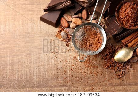 Sieve with aromatic cocoa powder, beans and pieces of chocolate on wooden background