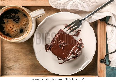 Wooden tray with delicious cocoa brownie on table