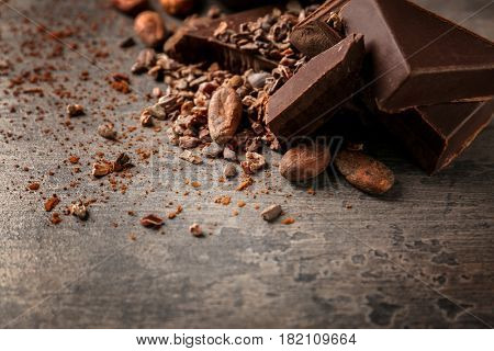 Cocoa beans and pieces of chocolate on table