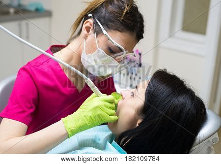 Female dentist cleaning teeth of a beautiful patient woman in dental clinic