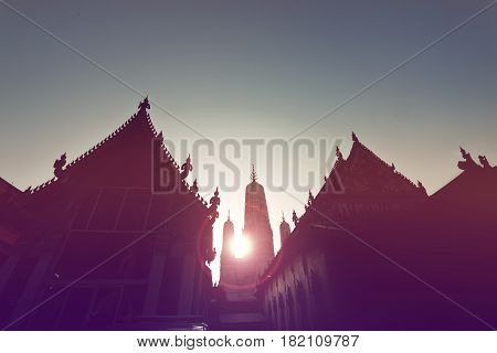 sunset at buddhist building silhouette of the chapel and pagoda of Wat Mahathat. Phetchaburi Province Thailand