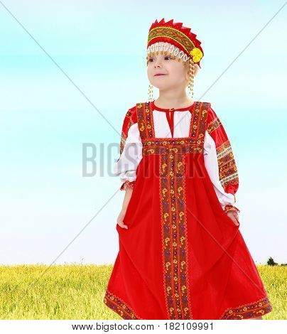 Cute little girl in Russian folk dress. She holds the edge of the dress by hand.