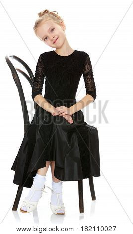 The slender little blonde girl dancer in the long dress of black color made specifically for performing .Girl sitting on an old Viennese chair with his leg over the other.Isolated on white background.