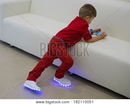 Small boy playing on smartphone. Mobile gaming. he is wearing glowing white led sneakers . Shoes with light.