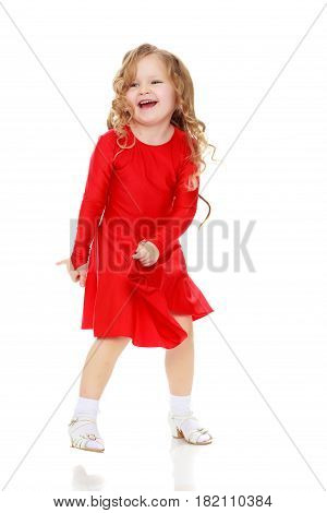 Beautiful, chubby little girl with long, blond, curly hair.Girl dancing in a bright red dress.Isolated on white background.