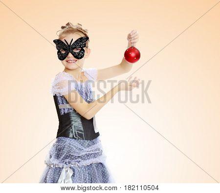Slender little girl , with beautiful hair on his head, elegant long Princess dress.Posing in carnival mask.She admires the beautiful Christmas decorations.