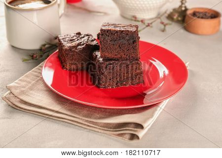 Plate with delicious cocoa brownies on table