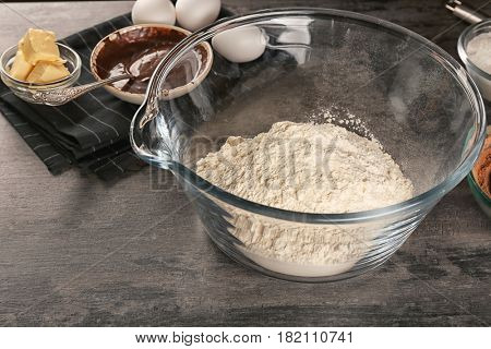 Bowl with flour for preparing  cocoa brownies on table