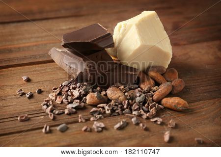 Cocoa beans, nibs and pieces of different chocolate on wooden background