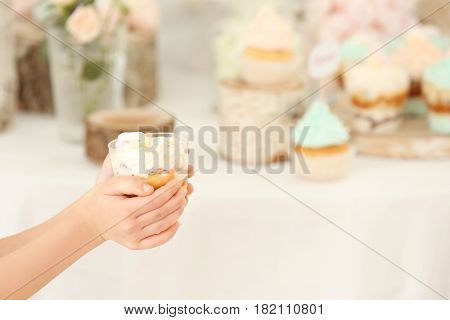 Hands of cute little girl with tasty dessert on blurred background