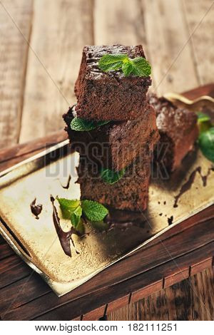 Metal tray with delicious cocoa brownies on wooden table