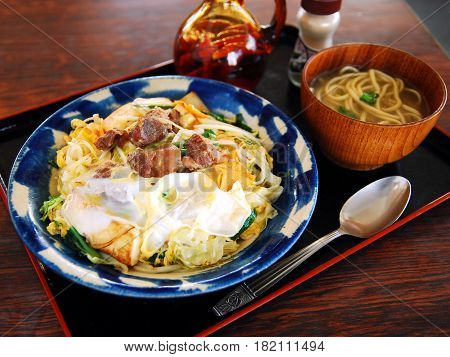 Udon Ramen Noodle With Egg And Beef On Wooden Table