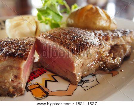 Delicious fried beefsteak on dish in restaurant
