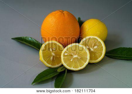 Organic lemon and orange on the gray background - Isolated
