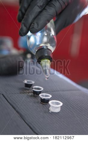Tattoo artist pouring solvent to small cups with ink. Closeup