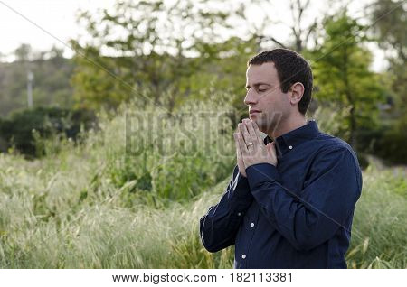 Praying man outdoors in a grassy field with hands together wearing a navy blue shirt.