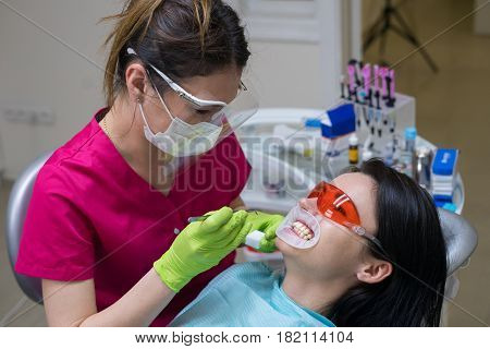 Close-up portrait of a female patient at dentist in the clinic. Teeth whitening procedure