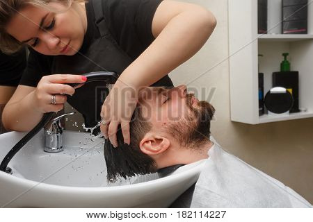 Professional hairdresser doing haircut men's hair. The hairdresser washes the head of the client. Beauty saloon. Male beauty. The client is a hipster.