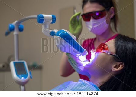 Close-up portrait of a female patient at dentist in the clinic. Teeth whitening procedure with ultraviolet light UV lamp.