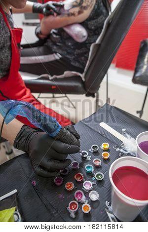 Woman tattoo artist refilling her pen. Closeup