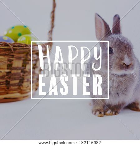 Easter greeting against basket with easter eggs and bunny