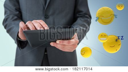 Digital composite of Business man mid section with tablet next to emojis and flare against blue background