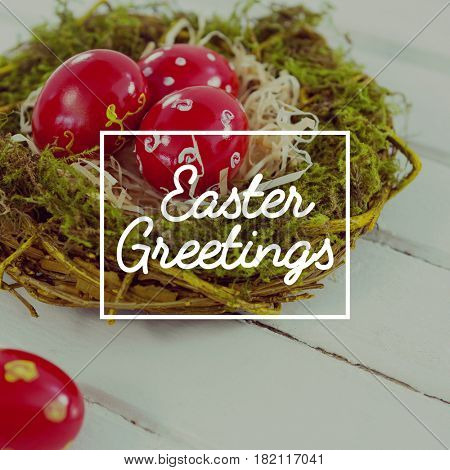 Easter greeting against red easter eggs in nest on wooden surface