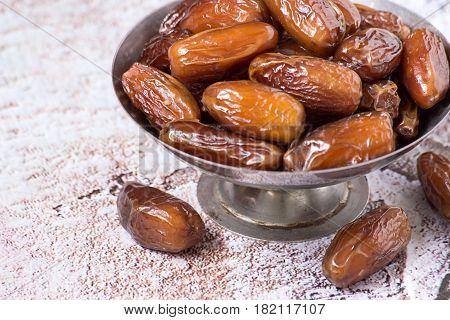 Healthy food. Dry sweet dates in a round metal vase.
