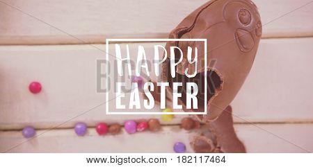 Easter greeting against broken chocolate easter egg on wooden plank