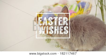 Easter greeting against basket with easter eggs and easter bunny
