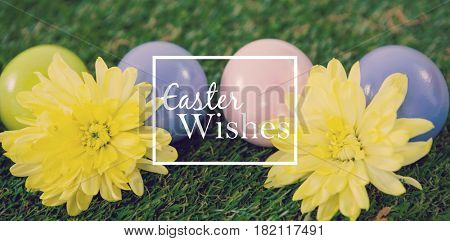 Easter greeting against multicolored easter egg with yellow flowers