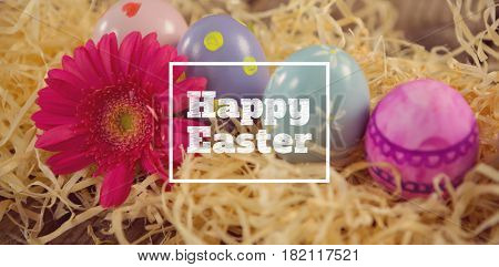 happy easter against painted easter eggs with flower in nest
