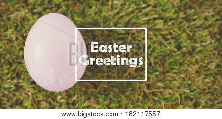 Easter greeting against white easter egg on grass