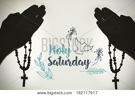 Easter message against solhouette hand with rosary praying