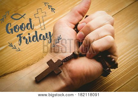 Easter message against hand holding rosary beads against wooden table