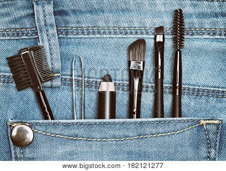 Eyebrow grooming tools in jeans pocket: brow comb, tweezers, eyebrow pencil, angled brushes, spooly brush. Toned image
