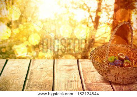Easter eggs in paper nest basket against tranquil autumn scene in forest