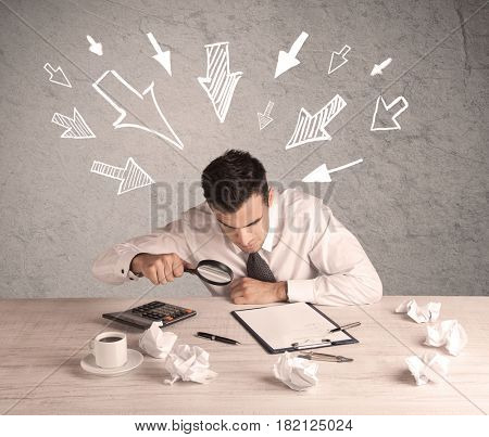 A young businessman sitting at an office desk and working on paperwork with drawn arrows pointing at his head concept