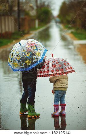 children walk in the rain holding umbrellas