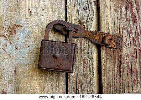Obsolete wooden door of old left house locked with padlock