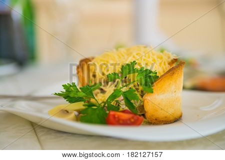 Close up restaurant dish warm salad with grated cheese on top served inside pieces of toasted bread
