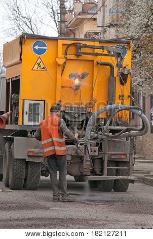 Construction workers during asphalting road works wearing coveralls