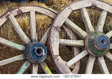 Close up two obsolete wooden wheels leaning on stacks of hay