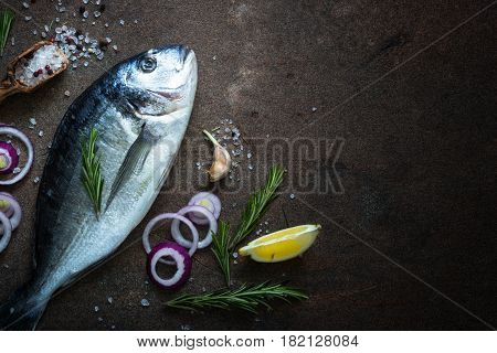 Fresh fish dorado. Dorado and ingredients for cooking at dark rusty table. Top view with copy space.
