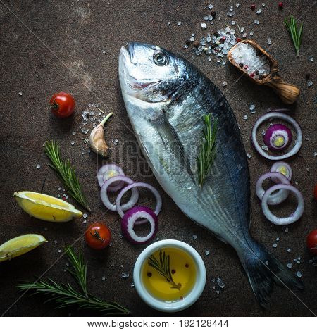 Fresh fish dorado. Dorado and ingredients for cooking at dark rusty table. Top view.