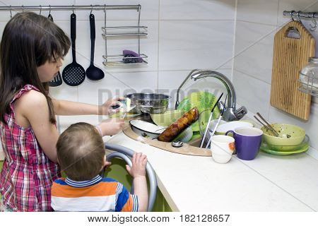 The child washes a bunch of dirty dishes standing near the sink.