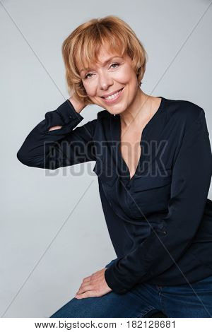 Image of a cheerful mature woman sitting and posing isolated over grey wall. Looking at camera.