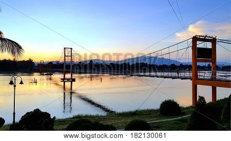 Tak Thailand Nov05 2015 : 200 year Rattanakosin Sompoch bridge (hanging bridge) across the ping River during colorful twilight sky. Tak province Thailand