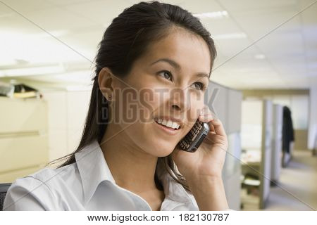 Eurasian businesswoman talking on cell phone in office