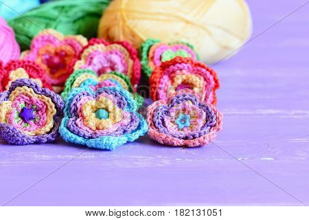 Crochet flowers embellished with buttons and beads. Beautiful crochet flowers, colored cotton yarn on purple wooden table. Easy summer floral crafts. Closeup